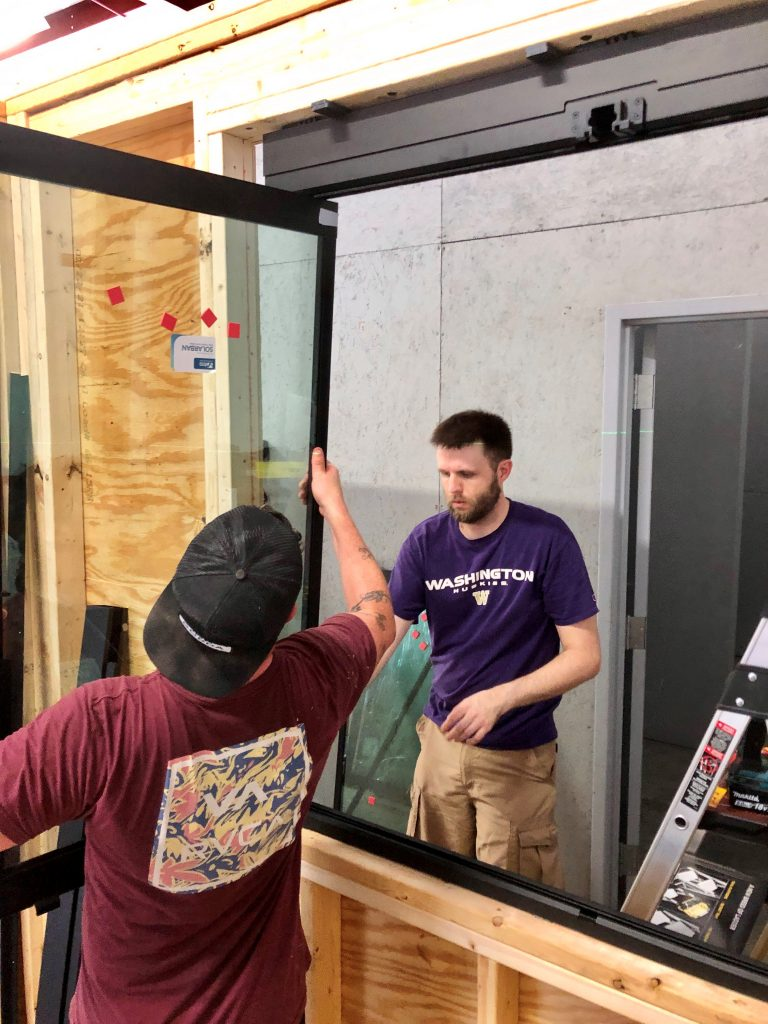 Industrial designer with Pillar design assists installer with Glass Expanse window